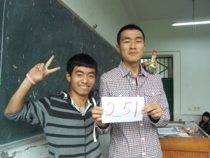 Monitor Elroy (tallest) hands out the prize to his classmate, who guessed 243 while the true number was 251.