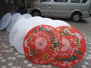 Recently glued and papered umbrellas, drying in the sun