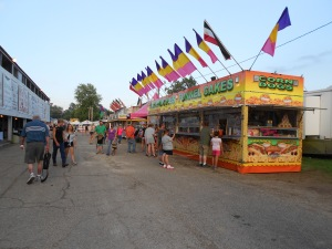 Ice-cream waffle cones, cheesy fries, pizza slices, cotton candy, home-dipped corndogs, pork burgers --- Walking this carnival roadway will lead to several unwanted pounds.
