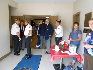 Entering the building, we have our greeters, American Legion members getting ready for the ceremony, and the poppy table to pick up your poppies.