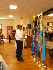 The Color Guard posts the colors (i.e., bring in the US flag and Legion flag)