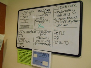 In the hospital room, a whiteboard is written on for information.
